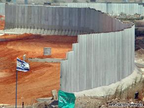 The barrier is seen during construction in 2002 separating the Cross Israel Highway from the West Bank.