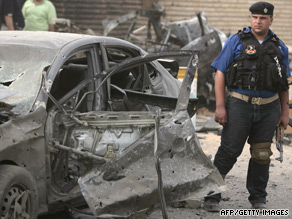 An Iraqi policeman stands next to the burned-out wreck of a car outside a Baghdad church July 13.