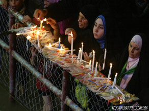 Shiite Muslim women light candles early Friday at a shrine in the holy city of Karbala, Iraq.