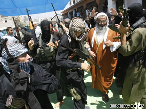 Armed members of the radical Islamist group Jund Ansar Allah surround a group representative in Rafah on Friday.