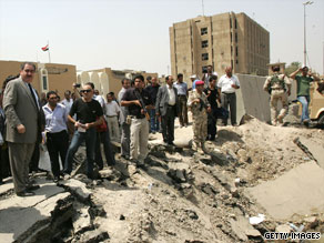 Iraqi Foreign Minister Hoshya Zebari, left, stands at the site of the ministry bombing that killed 32 employees Wednesday.