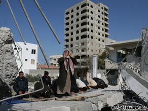 Palestinians pray on the rubble of a mosque destroyed in an Israeli strike in Gaza in February.