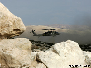 A military helicopter hovers over the Hebron Hills, site of the jet crash Sunday of Israel air force pilot Assaf Ramon.