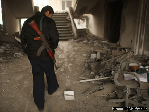 A member of Hamas walks through a building damaged during fighting with Israel in Gaza last January.