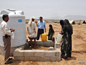 Women and children collect water at camp in northern Yemen for those displaced by fighting.