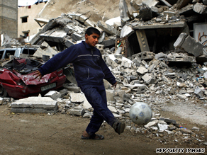 A Palestinian boy kicks a football outside damaged homes in northern Gaza in January 2009.