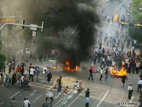 Supporters of Iran's opposition set flaming barricades in the street during a protest in June.