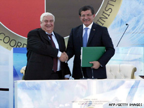Turkish Foreign Affairs Minister Ahmet Davutoglu, right, meets with Syrian counterpart Walid Muallem Tuesday.
