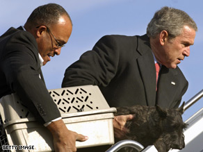 President Bush and an aide carry the First Cat and First Dog onto Air Force One, when both pets occupied the White House.