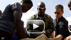 Haitian-born singer Wyclef Jean and actor Matt Damon distribute food to flood victims after four tropical storms hit the area in Gonaives, Haiti, Sunday, Sept. 14.