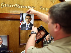 A U.S. Navy officer replaces the photo of former President George W. Bush with a photo of President Obama Tuesday after Obama's swearing in.