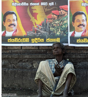 An elderly Sri Lankan man sits under posters on a street in Colombo on January 4, 2009, featuring an image of Sri Lankan President Mahinda Rajapakse and hailing the military's capture of the Tamil Tiger political headquarters.