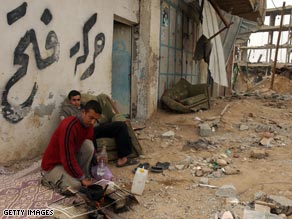 Palestinians sit next to Israeli-bombed buildings in Rafah, in the Gaza Strip.