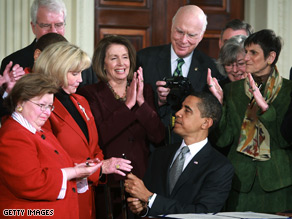President Obama hands a pen used to sign the Lilly Ledbetter Fair Pay Act to Ledbetter, second from left.