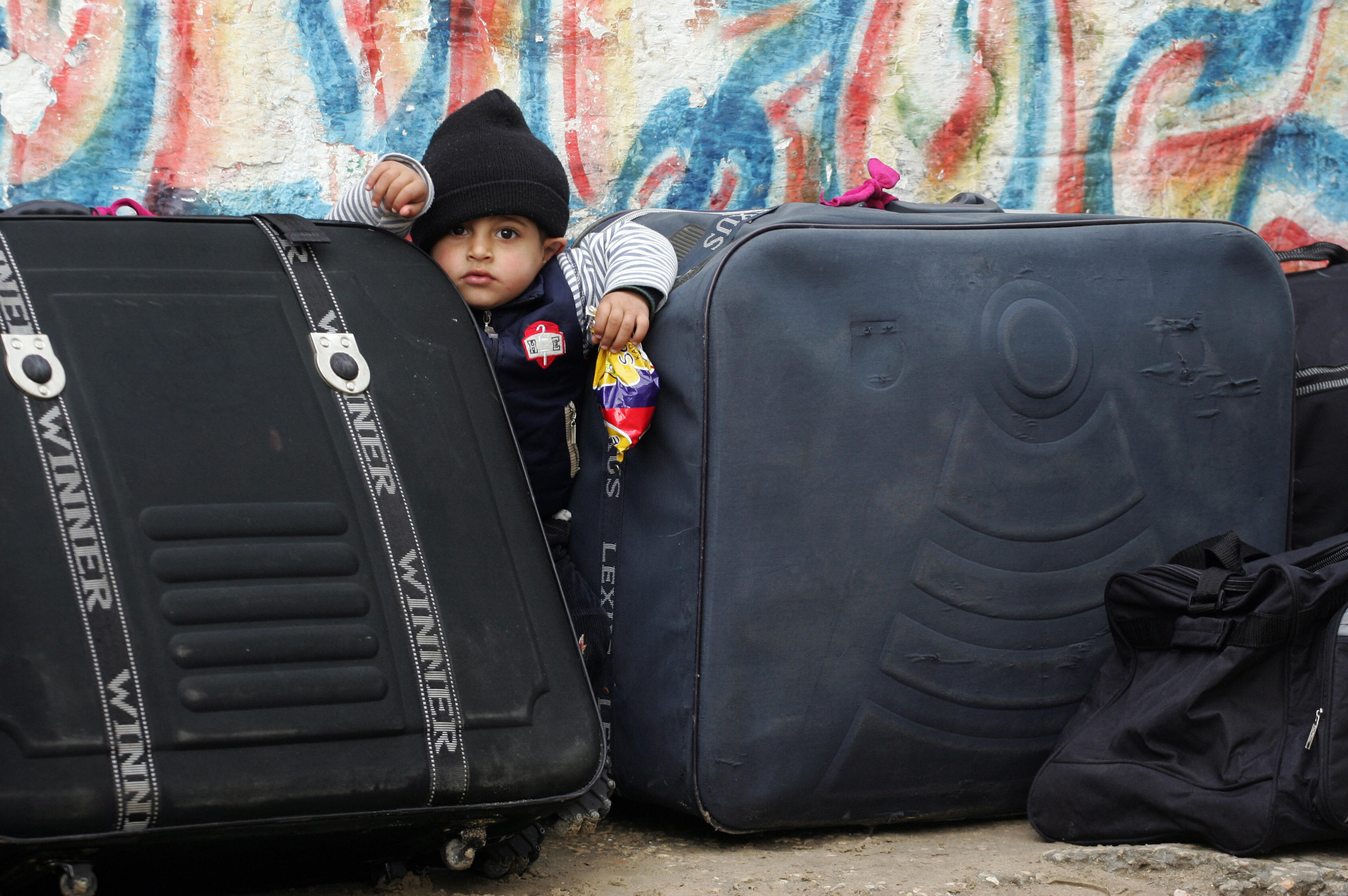 SAID KHATIB/AFP/Getty Images. A Palestinian toddler stands between suitcases he waits with family members to cross into Egypt from the southern Gaza Strip border crossing at Rafah. The border between Gaza and Egypt, the sole crossing that bypasses Israel, was opened on February 22 for three days to allow the passage of students and the sick.