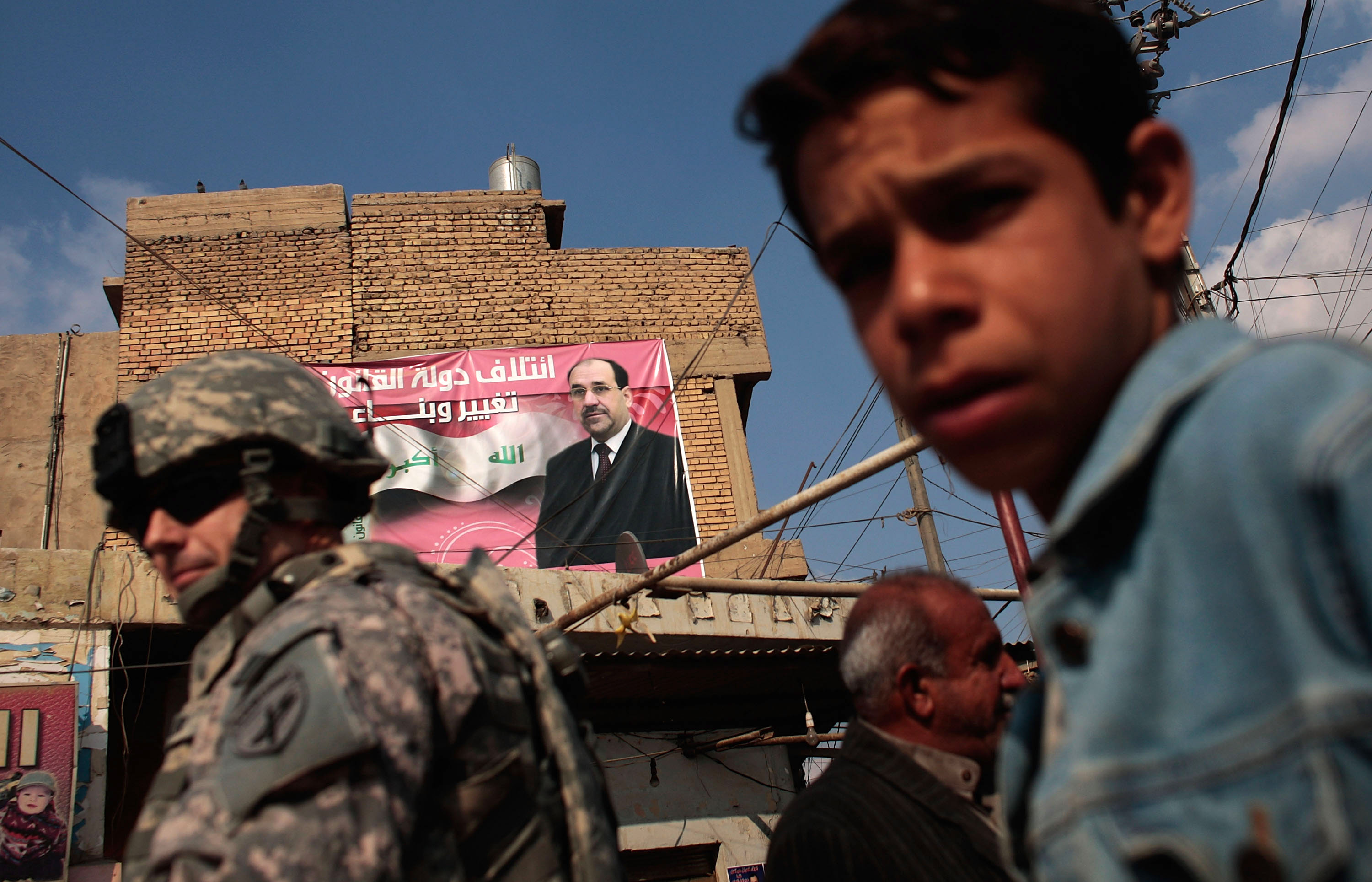 Chris Hondros/Getty Images. A boy and a soldier in the U.S. Army's 172nd Brigade Combat Team stand near a campaign poster touting Iraqi Prime Minister Nouri al-Maliki in Musayyib, in the Babil Province, Iraq.