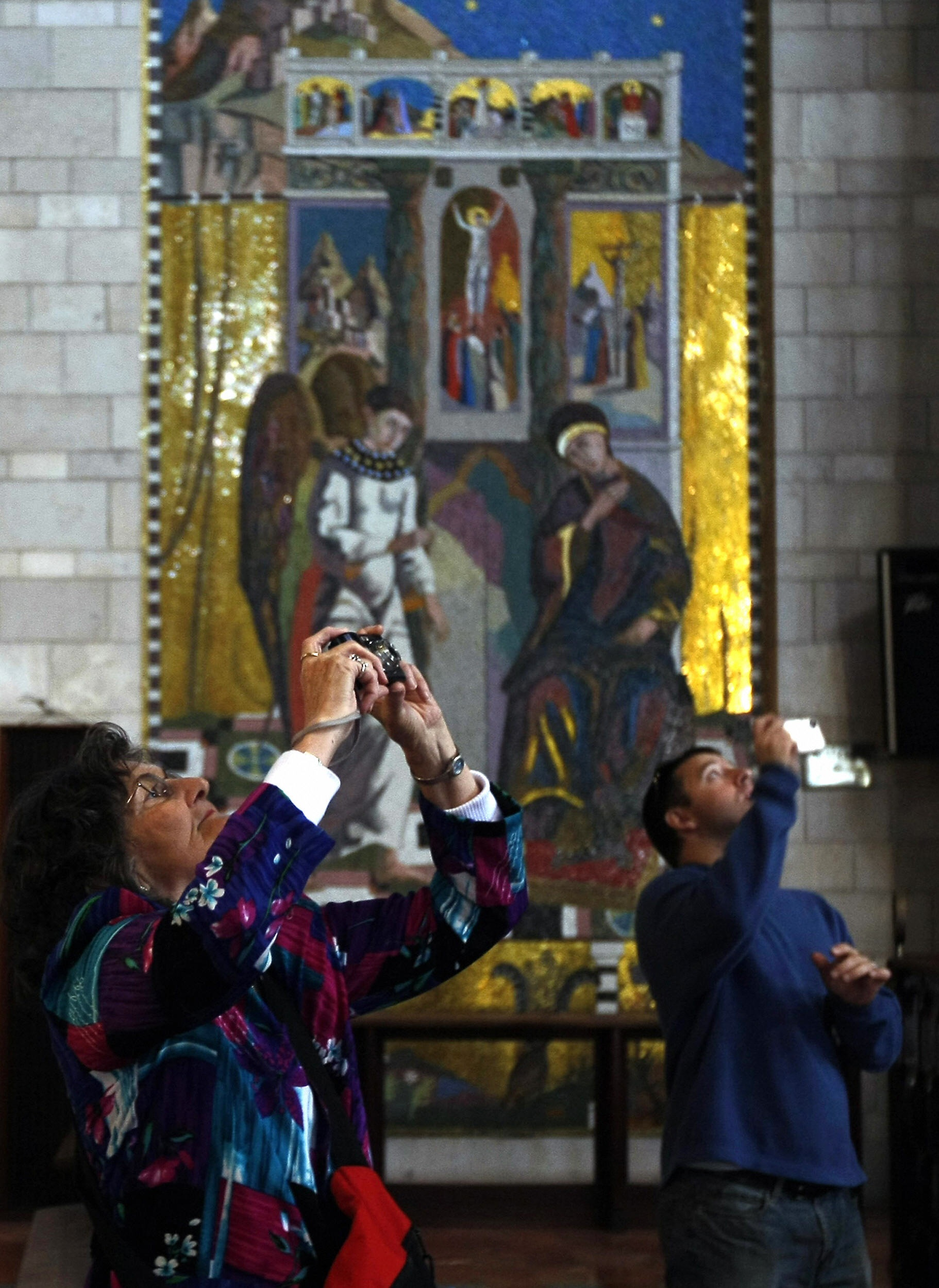 MENAHEM KAHANA/AFP/Getty Images. Christian pilgrims take pictures at the Church of the Annunciation.