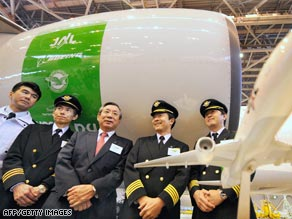 JAL President Haruka Nishimatsu, center, shares a light moment in front of a jet engine.