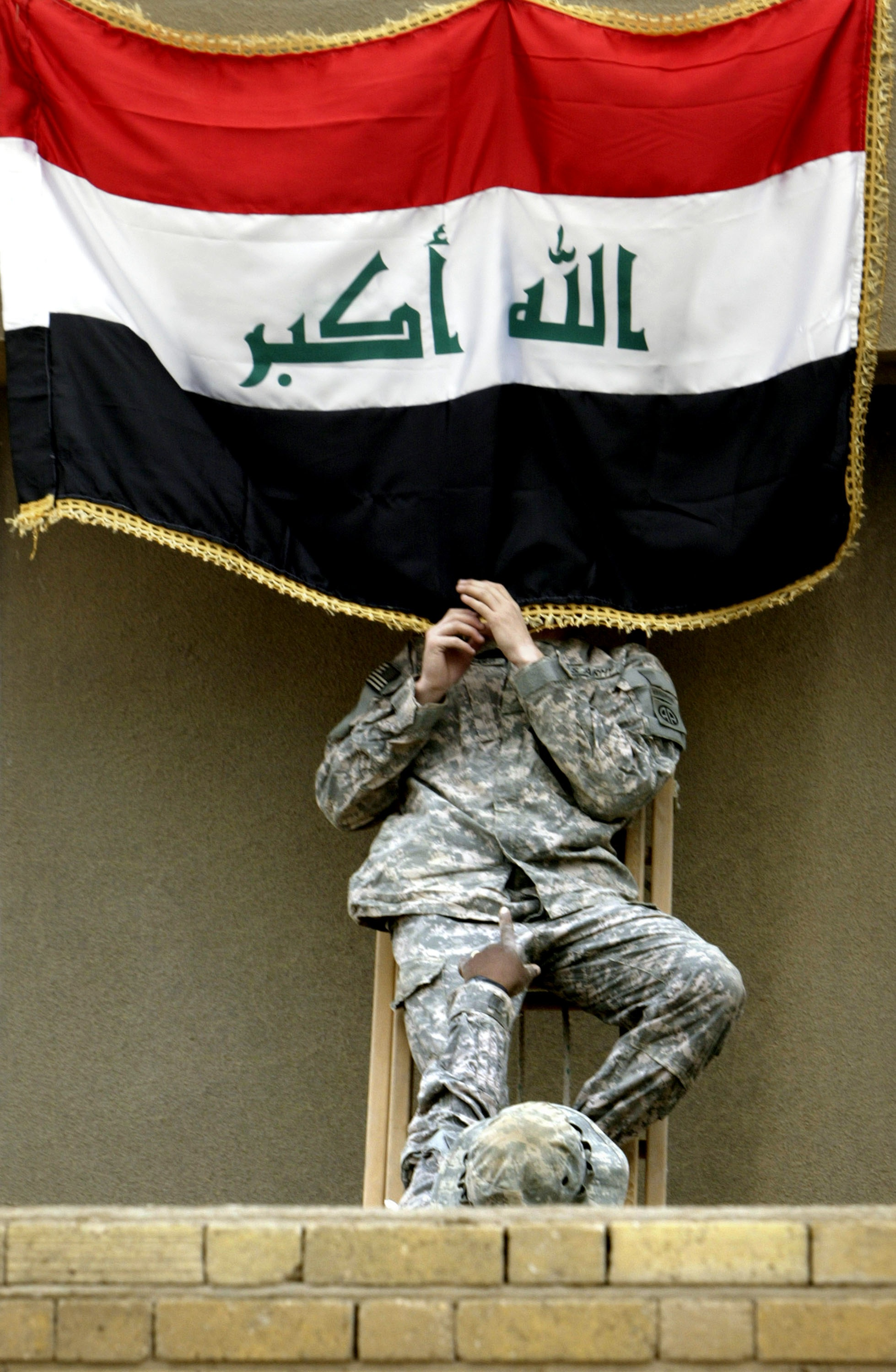 Wathiq Khuzaie/Getty Images. BAGHDAD, IRAQ, MARCH 31: A U.S army soldier prepares an Iraqi flag during a handover ceremony at Camp Rustimiyah March 31, 2009 in Baghdad, Iraq.