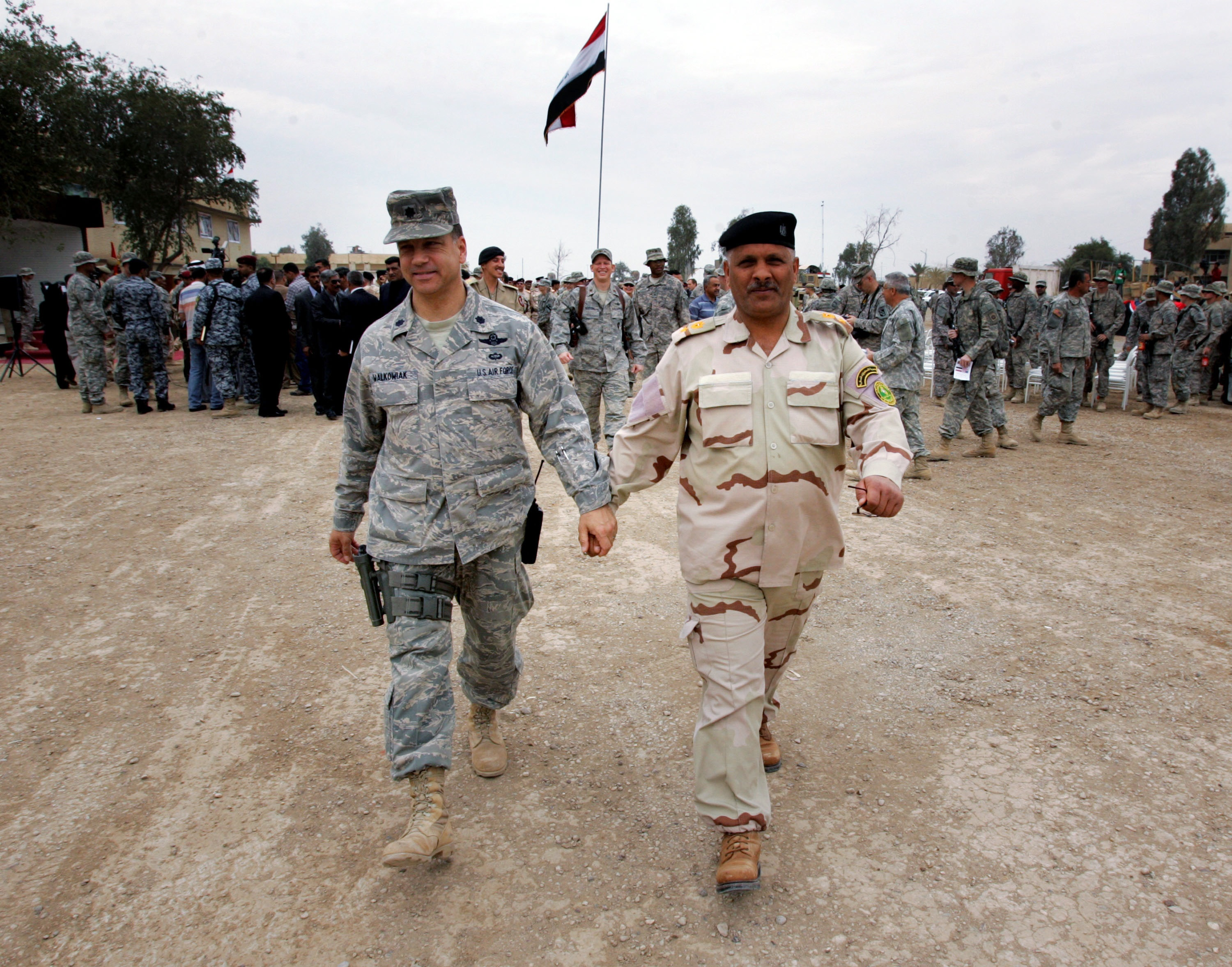 Wathiq Khuzaie/Getty Images. BAGHDAD, IRAQ, MARCH 31: An Iraqi Army officer (R) holds the hand of a U.S Army officer during a handover ceremony at Camp Rustimiyah March 31, 2009 in Baghdad, Iraq.