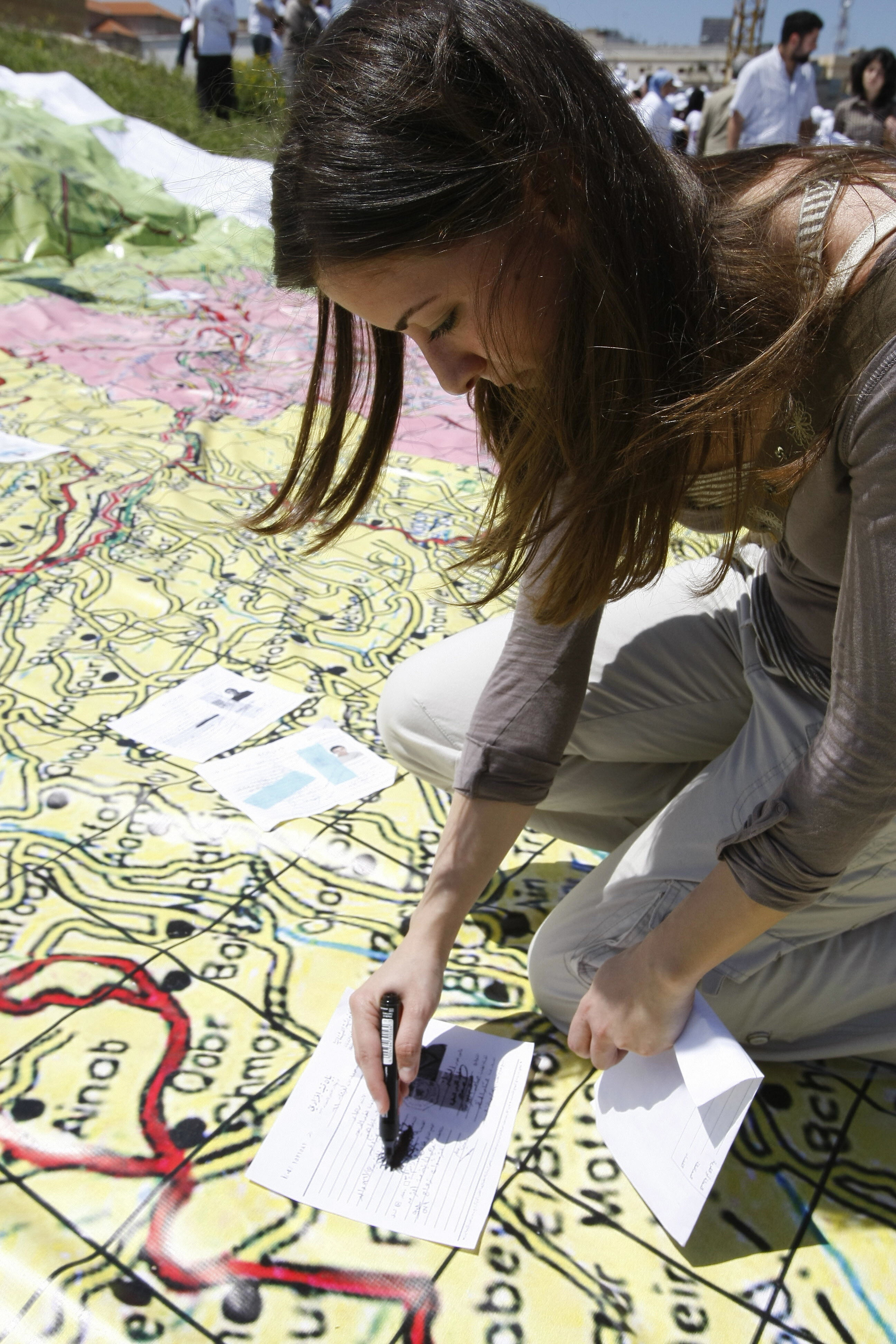 RAMZI HAIDAR/AFP/Getty Images.A Lebanese woman crosses over the religion field on her civil registry record after placing it on the spot where her hometown is located on a large map during a gathering organised by civil society associations on the occasion of the 34th anniversary of the outbreak of the Lebanese civil war (1975-1990), in downtown Beirut on April 13, 2009. Lebanese Interior Minister Ziad Baroud issued a memorandum in February dispensing citizens from revealing their religious affiliation on civil registry records. Rights groups have been pushing for such a measure since the end of Lebanon's 1975-1990 civil war when many were killed at roadblocks based on the religion noted on their ID cards.