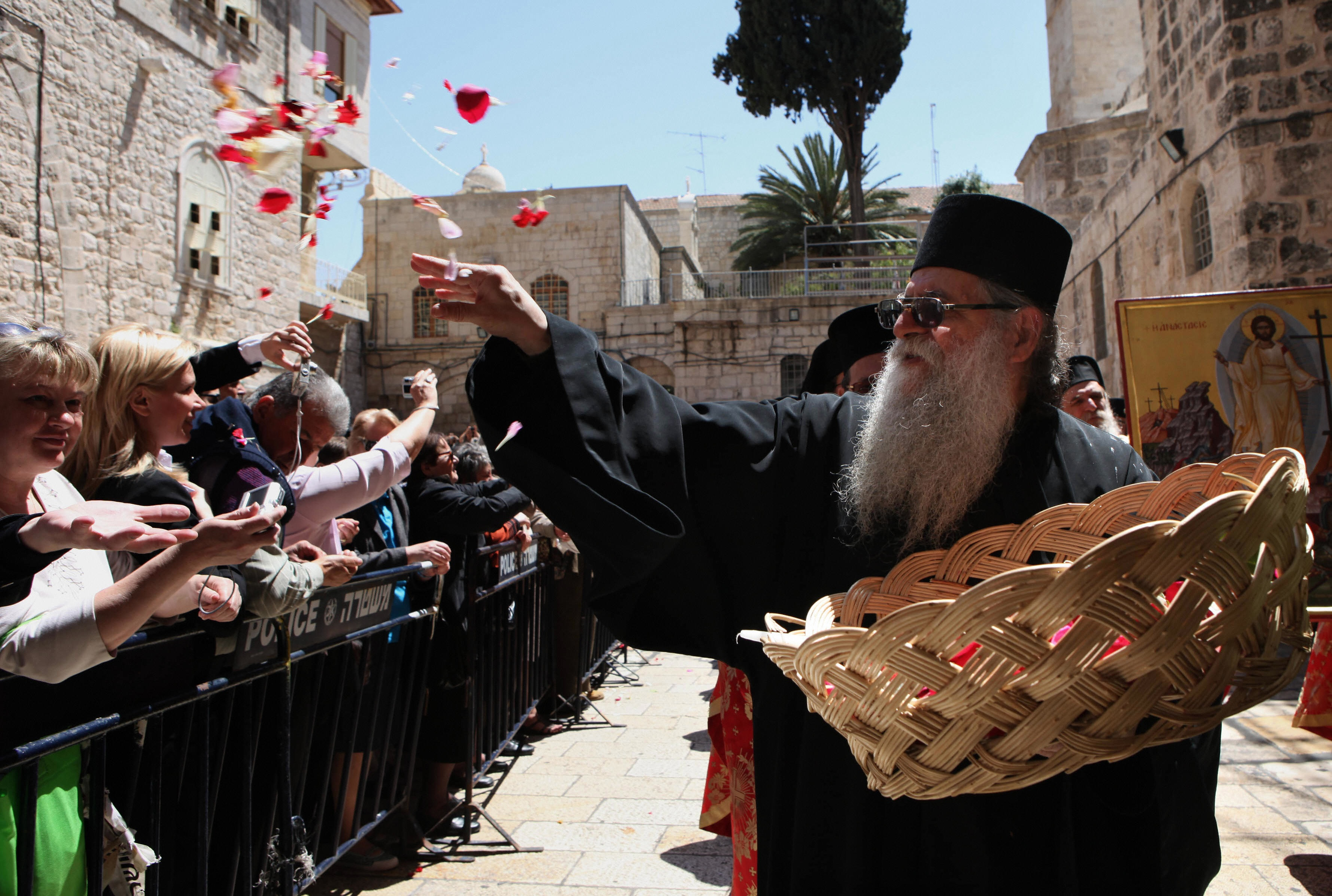 GALI TIBBON/AFP/Getty Images. A Greek Orthodox priest throws rose petals at pilgrims in front of the church of the Holy Sepulchre during the Easter Sunday procession in Jerusalem's Old City on April 19, 2009.