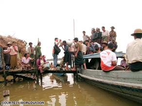World Vision relief workers travel from village to village to distribute emergency supplies.  In the months following the storm, there was often not enough land in the water-logged country to distribute supplies, so aid agencies would travel by boat.