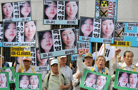 South Korean conservative activists hold up pictures of US journalists Laura Ling and Euna Lee, detained by the authorities in North Korea, during a rally calling for their freedom in Seoul on June 4, 2009. Getty Images