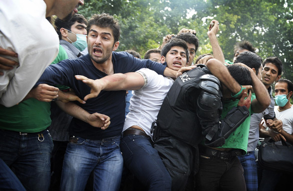 Supporters of defeated Iranian presidential candidate Mir Hossein Mousavi help evacuate an injured riot police officer after he was beaten by demonstrators during a protest in Valiasr Street in Tehran on June 13, 2009. Getty Images