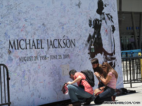 Fans sign a mural near Staples Center in Los Angeles, California Sunday.