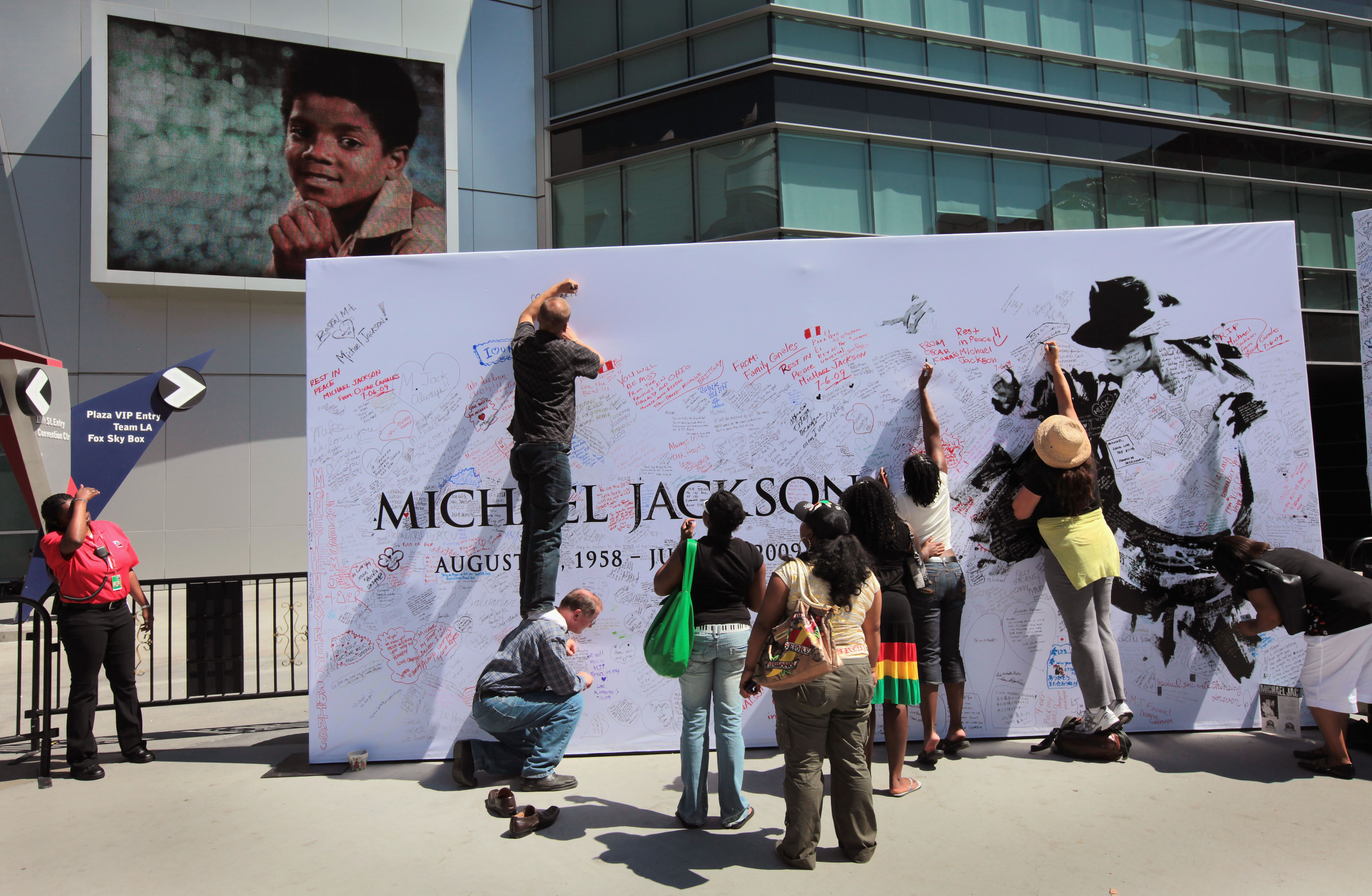 (Getty Images) Fans sign a Michael Jackson poster covered in messages outside the Staples Center.
