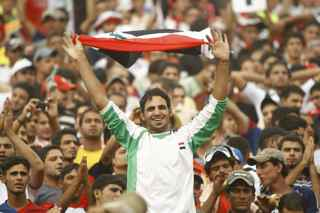 AHMAD AL-RUBAYE/AFP/Getty Images. An Iraqi fan celebrates during the friendly match Iraq versus Palestine at the al-Shaab Stadium in central Baghdad on July 13, 2009. Iraq won 4-0.