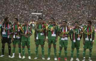 AHMAD AL-RUBAYE/AFP/Getty Images. Members of the Iraqi team line up at the start of their friendly match Iraq versus Palestine at the al-Shaab Stadium in central Baghdad on July 13, 2009. Iraq won 4-0.