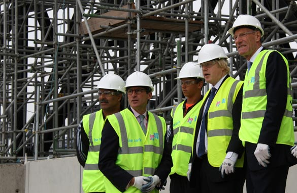 Dignitaries including London Mayor Boris Johnson and the chairman of the London 2012 Olympic Committee Seb Coe look at the stadium rising from the mud.