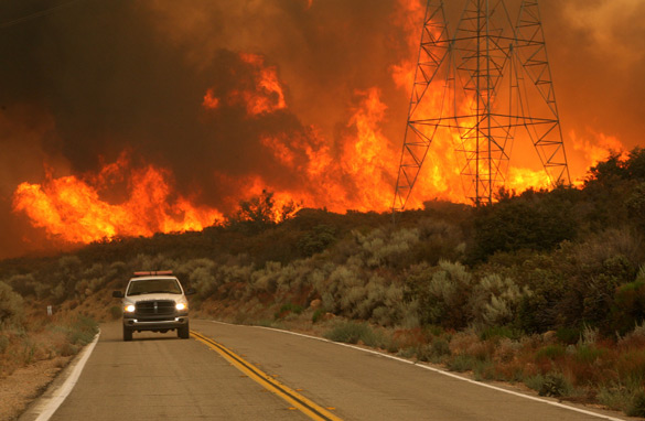 A firefighter drives away from a wall of flames August 30, 2009 in Acton, California. (Getty Images)