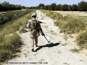 A U.S. Marine sweeps for Improvised Explosive Devices (IED's) along the pathways around their base at Camp Jaker.