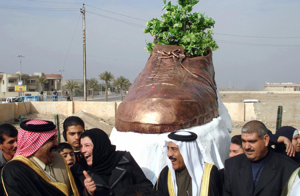 Iraqis unveil a bronze monument of a show thrown at U.S. President George W. Bush. (PHOTO: AFP/GETTY IMAGES)