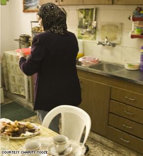 Hana Al Badree making lunch in her Heshmi Shamali temporary home in Amman, Jordan.