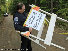 A Mont Vernon police officer moves a barricade before leaving the scene of the homicide on Monday.