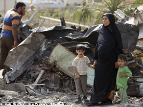 An Iraqi woman and her two little boys survey the damage after a suicide truck bomb struck in central Baghdad over the weekend. The near-simultaneous twin suicide vehicle bomb attacks were the deadliest in the violence-wracked country in over two years.
