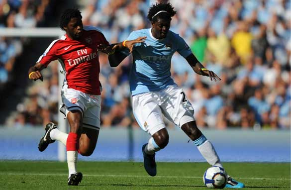 Adebayor is challenged by former team-mate Alexandre Song.