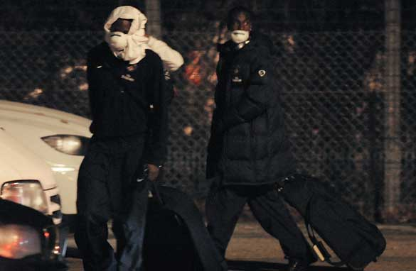 Masked Paris Saint-Germain players head home after an inter-squad outbreak of swine flu causes their game with Marseille to be postponed.
