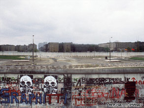 Graffiti is painted on Berlin Wall on West Berlin side while East German and Soviet flags fly on the other side of the East Berlin no-mans-land spiked with anti-tanks traps.