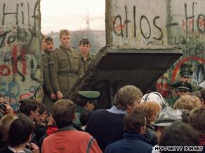 West Berliners crowd in front of the Berlin Wall as they watch East German border guards demolish a section of the wall.