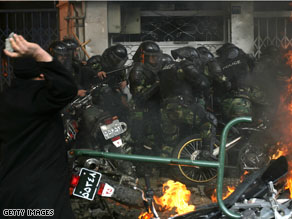 Police motorcycles burn as an Iranian opposition protester aims a stone at security forces during clashes in Tehran