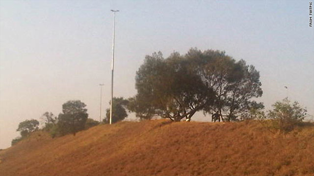The Twitter user @PigSpotter posts photos and locations of cops in South Africa. This TwitPic shows a cop behind a tree.