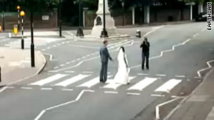 A bride and groom pose at Abbey Road in London, England.