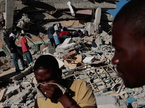 Haitians pass in front of the multi-story St. Gerard School that collapsed, leaving what is feared to be dozens trapped or killed under the rubble in Port-au-Prince.