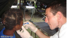 A medic at the IDF Field Hospital in Port-au-Prince checks on an injured child.