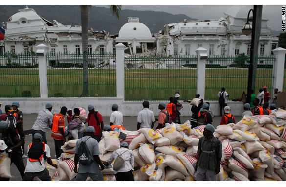 Haitians are given bags of rice in front of the National Palace Monday in central Port-au-Prince, Haiti.